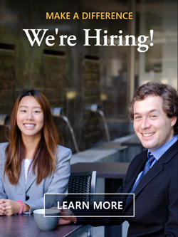 Learn more about making a difference. We're hiring! Image of two employees outside drinking coffee.